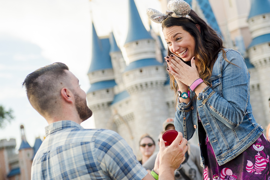 Couple getting engaged in front of Cinderella Castle