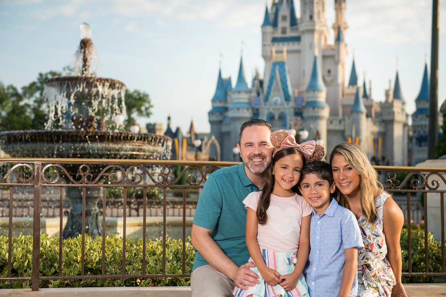 Family posing in front of Cinderella Castle